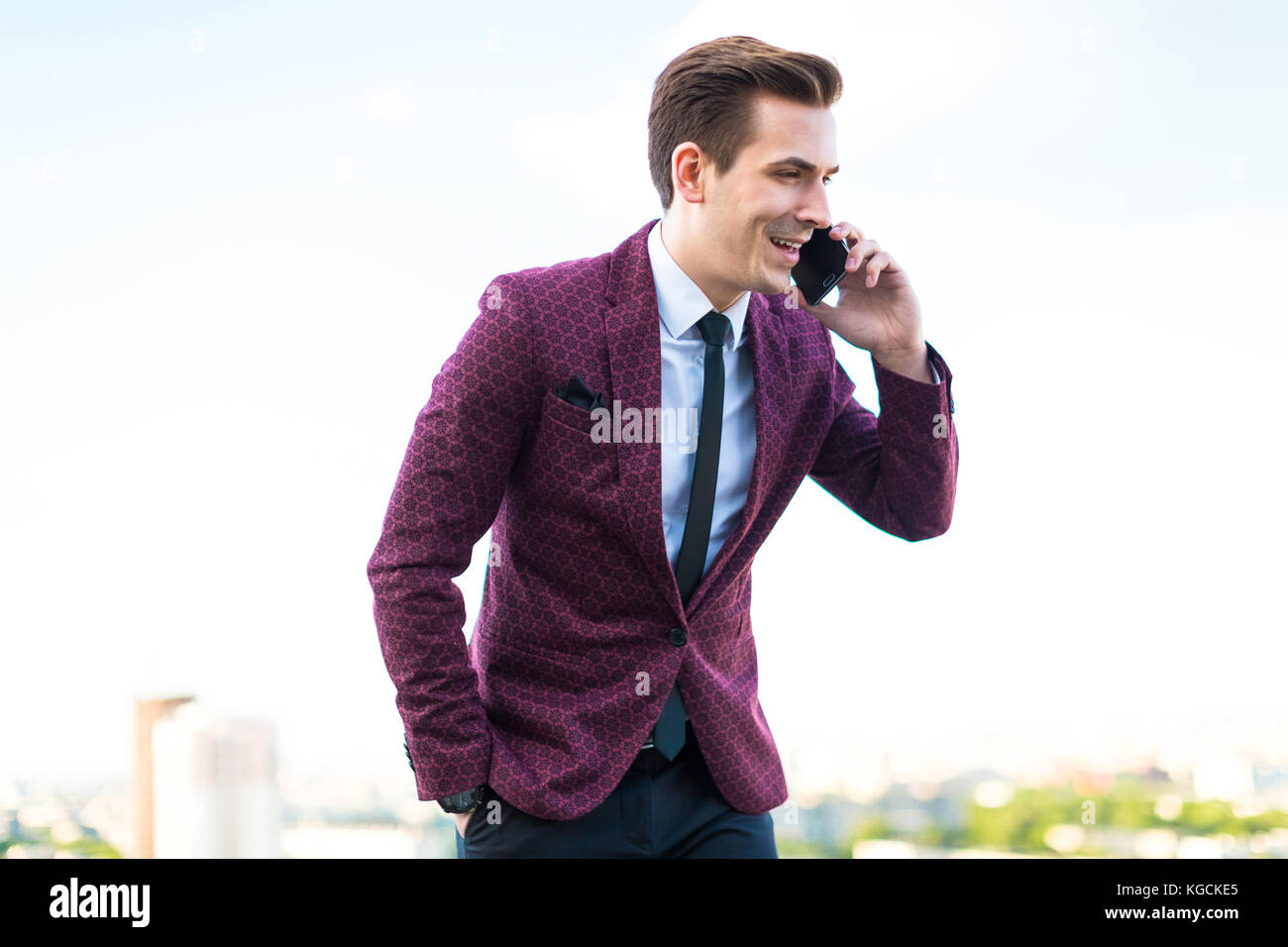 Young serious businessman in red suit and shirt with tie stand o Stock Photo