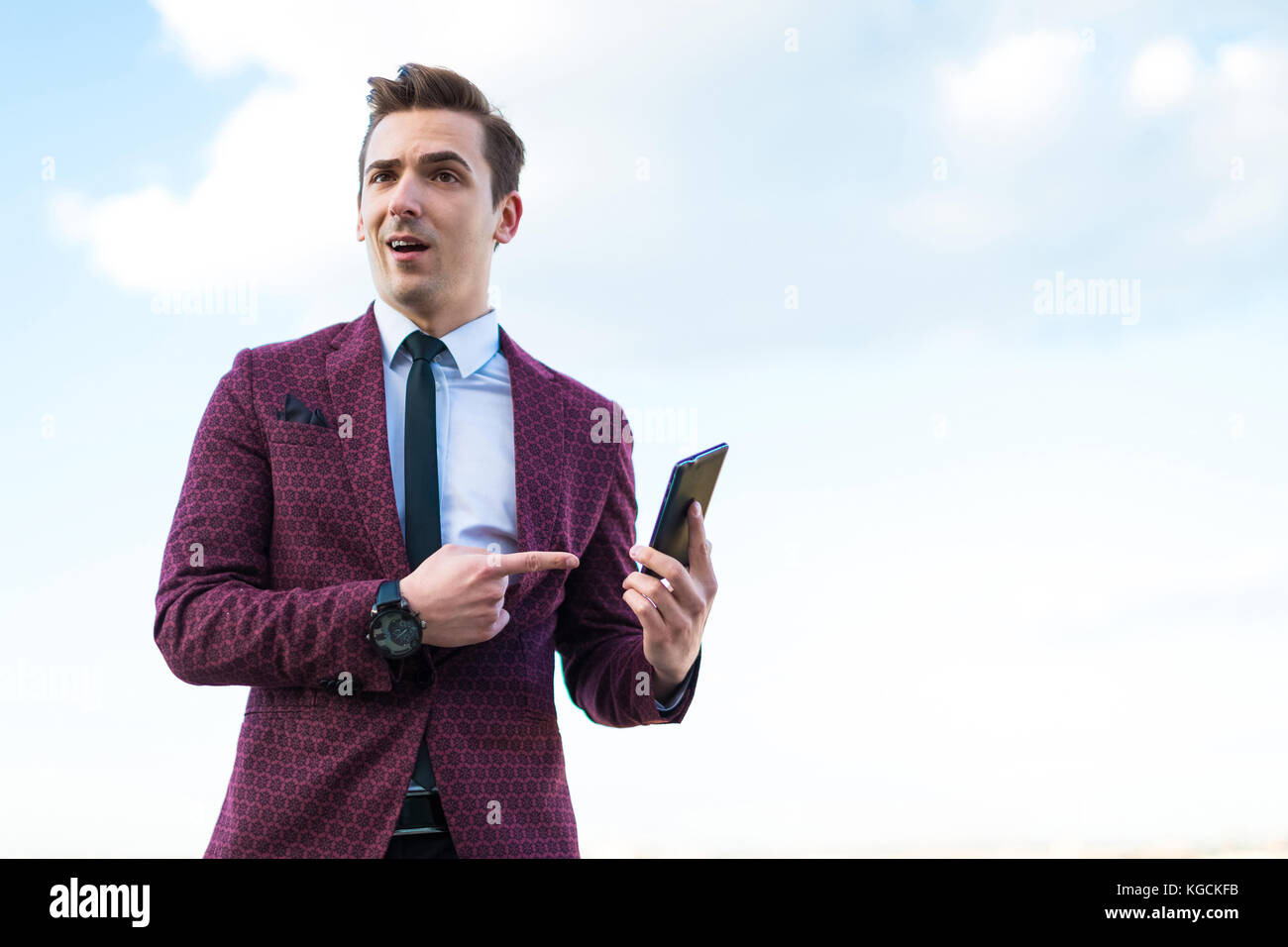 Young serious businessman in red suit and shirt with tie stand o - Stock Image
