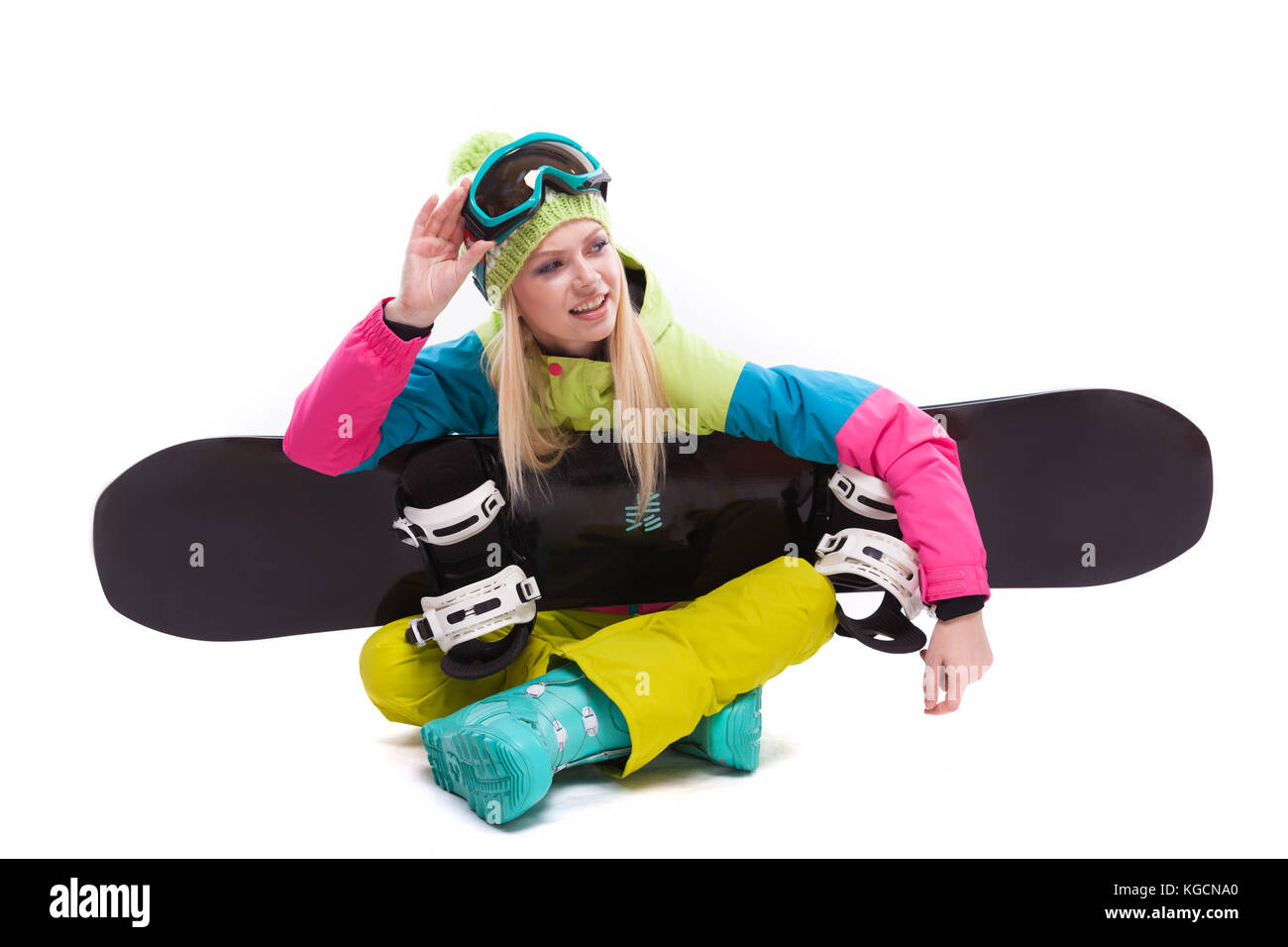 beauty young woman in ski suit and ski glasses sit with sbowboar - Stock Image