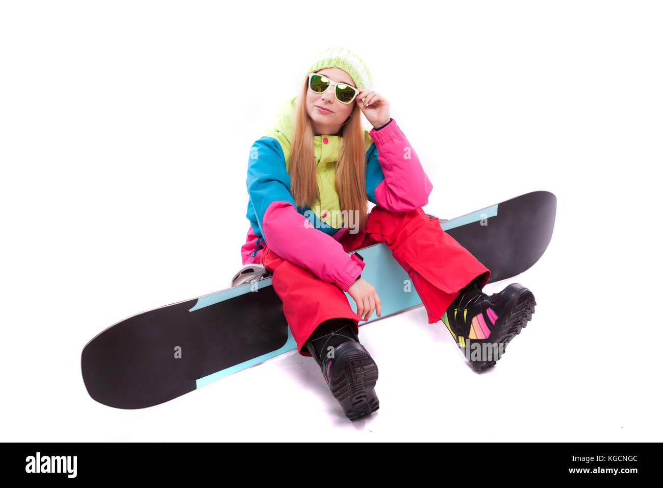 pretty young woman in ski outfit and sunglasses hold snowboard - Stock Image