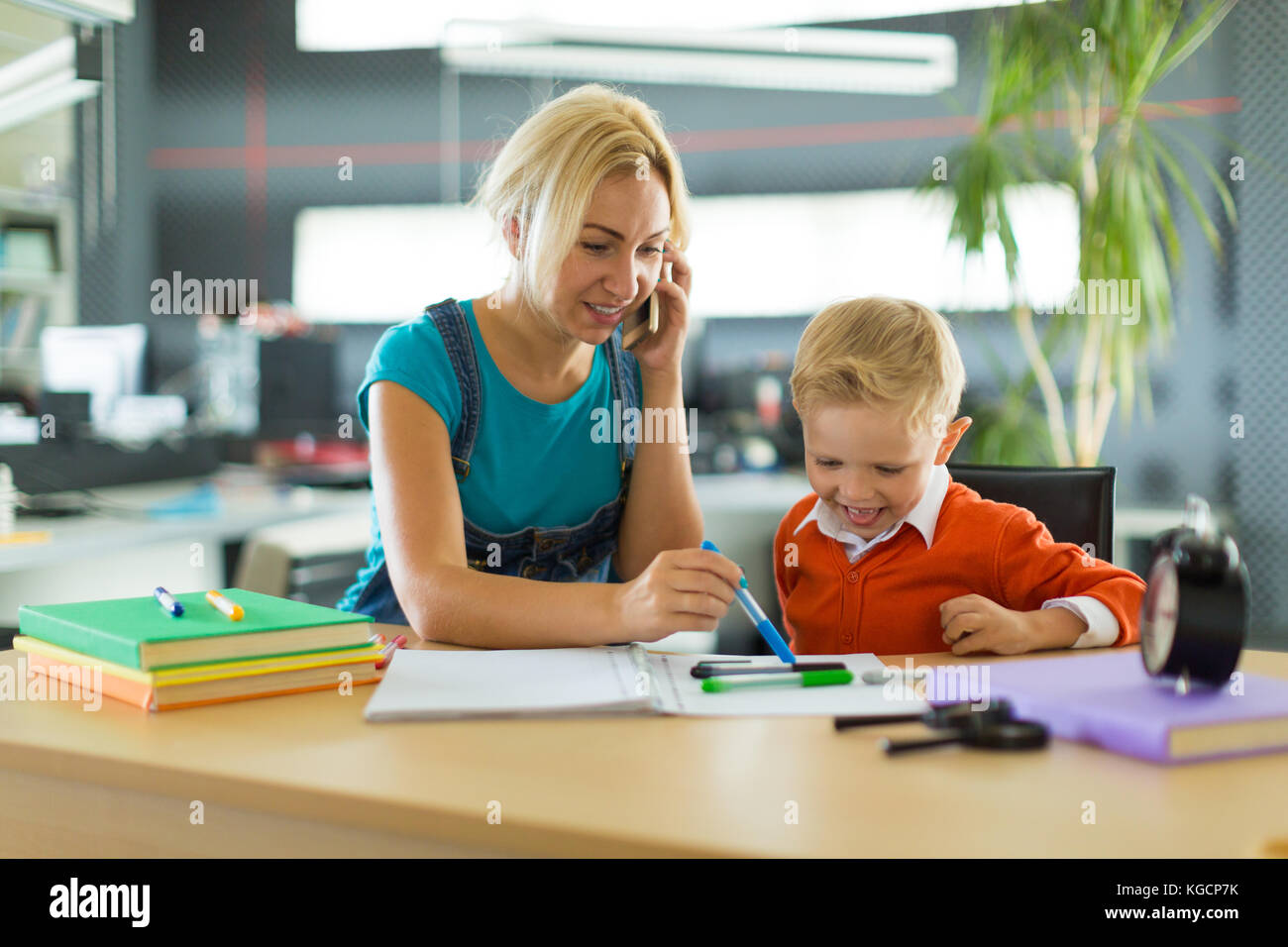 Cute boy and woman sit at the desk in the office - Stock Photo