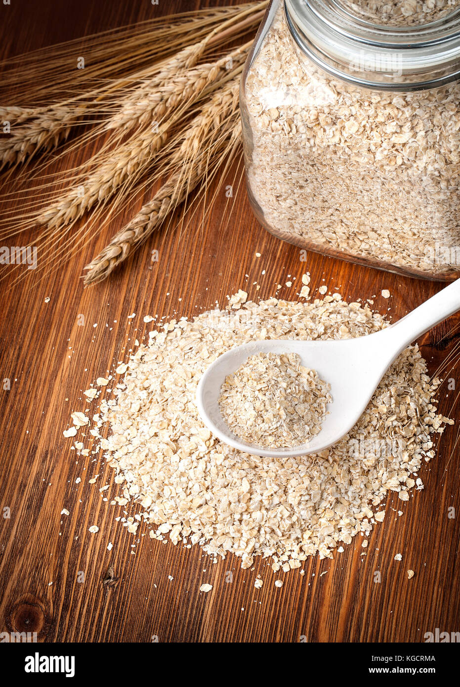 organic and nutritious oatmeal, glass jar,white spoon and ears of corn onwooden  background, - Stock Image