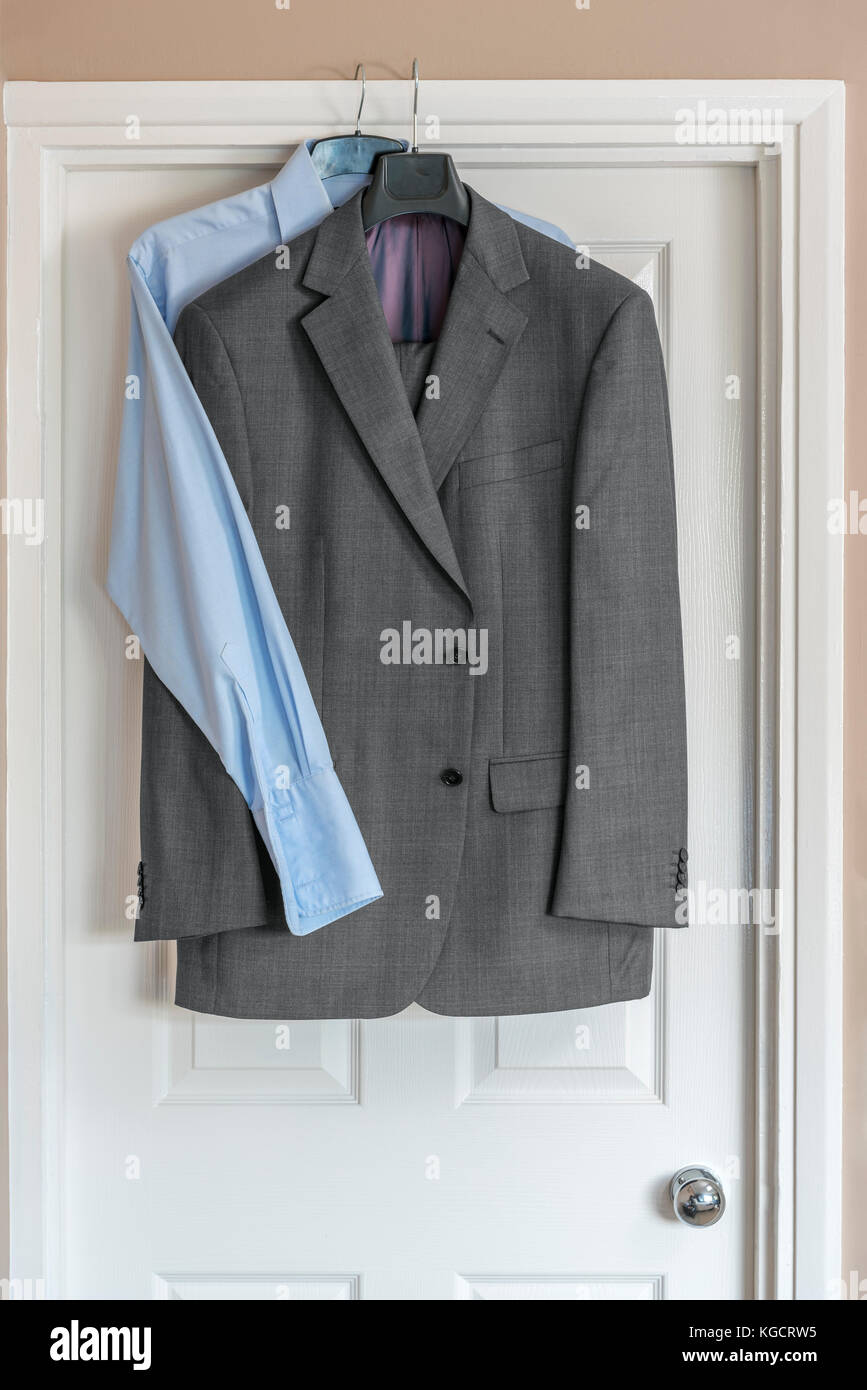 Mens formal business suit hanging over doorway, with blue shirt. - Stock Image