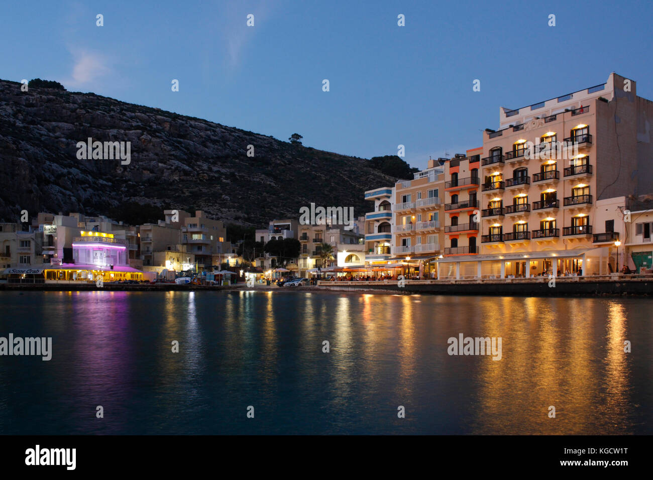 The seaside village of Xlendi (pronounced Shlendy) in Gozo, Malta, at dusk, with seafront hotels and restaurants - Stock Image