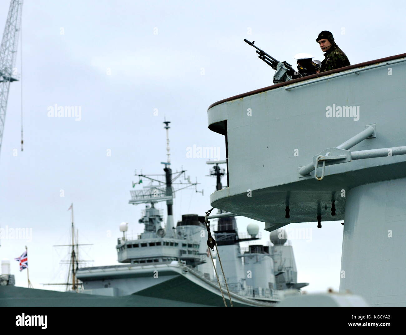 AJAXNETPHOTO. PORTSMOUTH, ENGLAND. - SECURITY LOOK-OUT - A ROYAL MARINE MANS A MACHINE GUN ON THE BRIDGE WING OF - Stock Image