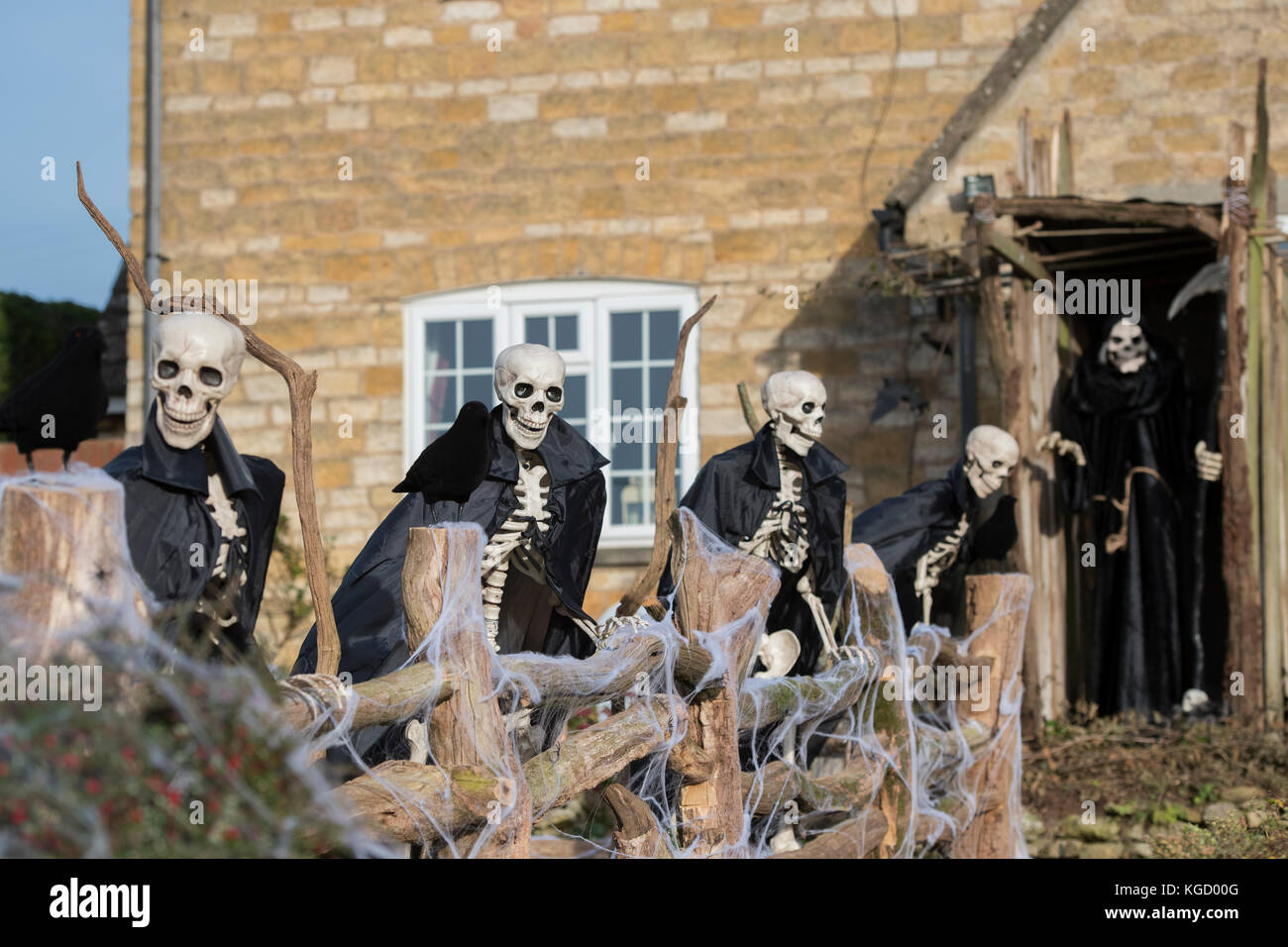 Halloween skeletons and grim reaper outside a house in Snowshill, Cotswolds, Gloucestershire, England - Stock Image