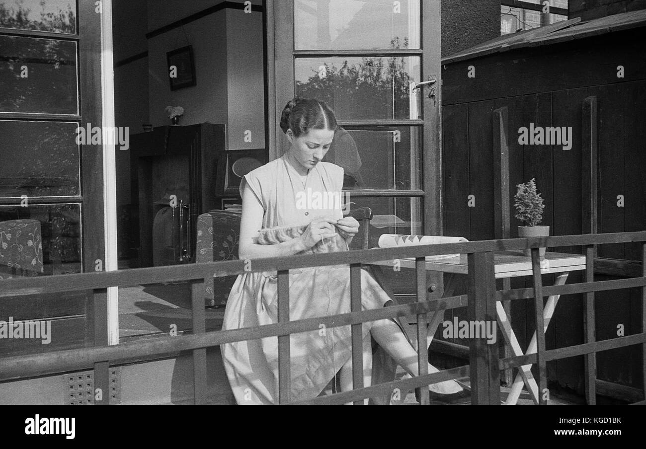 1940s, Britain, young lady a dress sitting alone on a home veranda knitting. Hand-knitting was a popular pastime - Stock Image