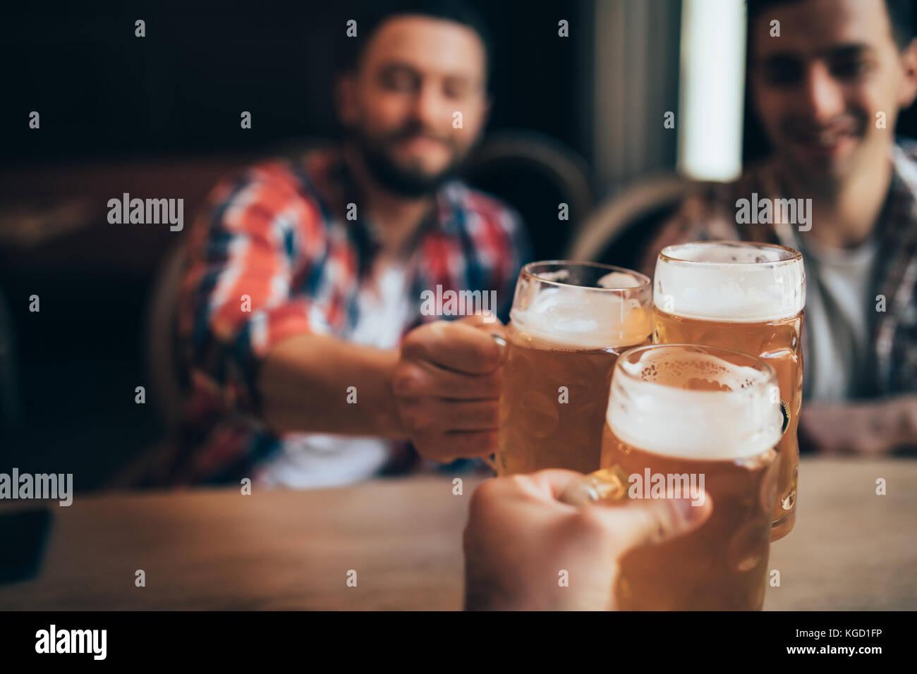 Hands Hold Beverage Beers Bottle Cheers in pub - Stock Image