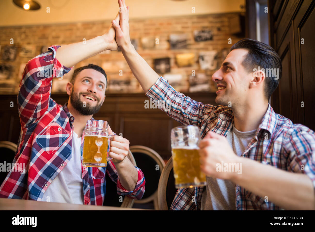 Happy young bearded man laughing high fiving his friend while having beer at the pub - Stock Image