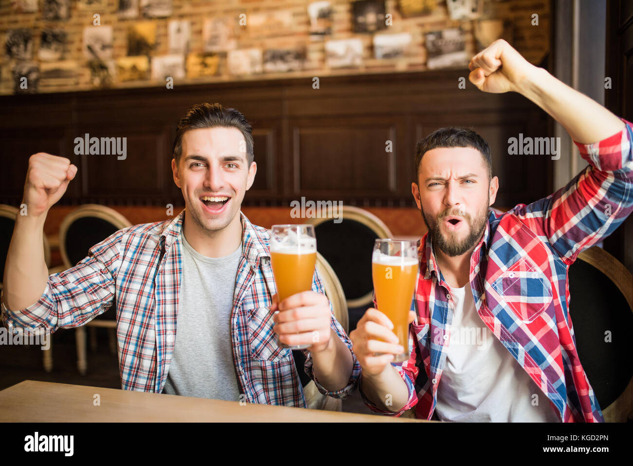 Cheerful male friends having fun at the beer pub celebrating victory of their favorite team watching game on TV - Stock Image