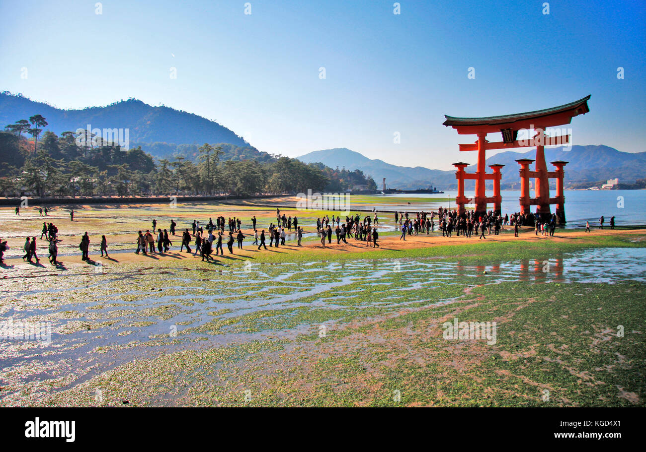Crowds gatering under a Torii gate whilst the tide is out. - Stock Image