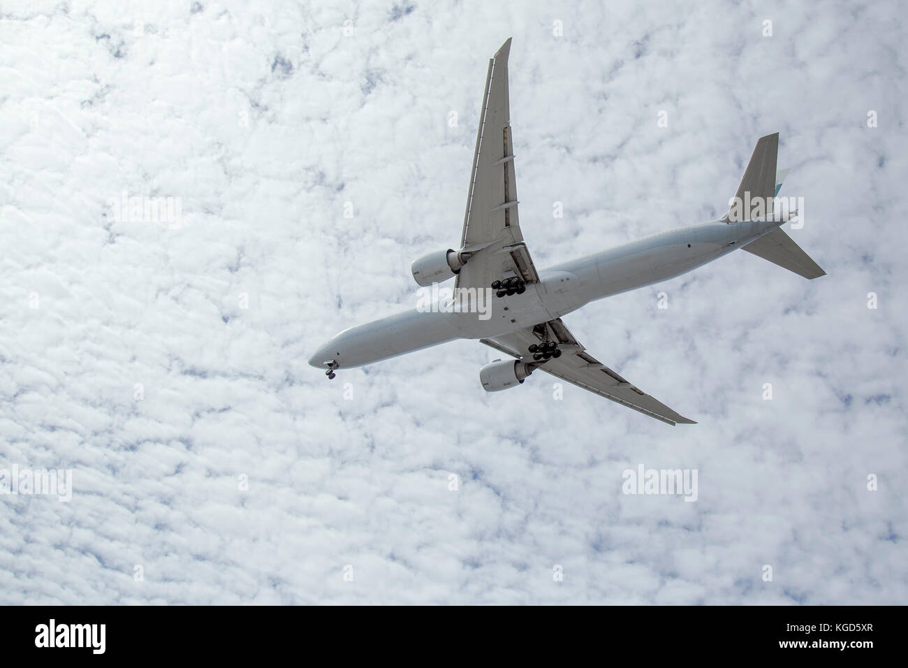Commercial airliner flying overhead preparing for landing at LAX with brilliant clouds in the background - Stock Image