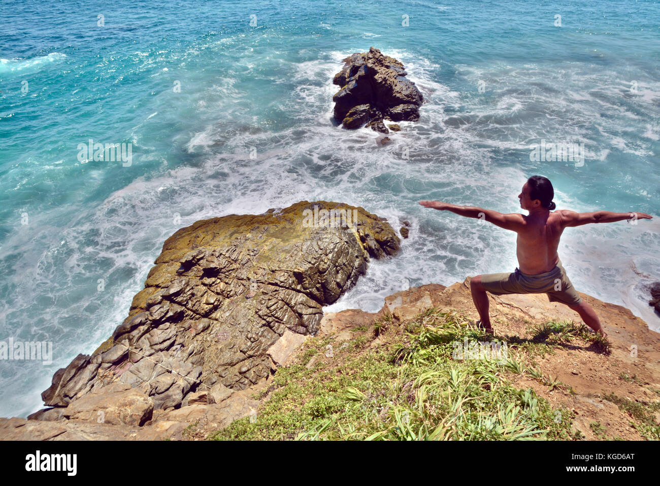 Middle-Aged asian man exercises with Hatha Yoga warrior Pose  in front of beautiful blue sea in Mexico - Stock Image