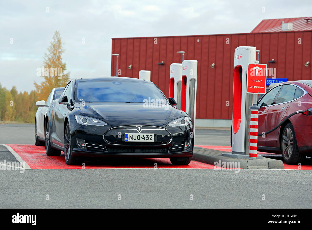 TOIJALA, FINLAND - OCTOBER 17, 2015: Three Tesla Model S cars are being charged at Tesla Supercharger station. Currently - Stock Image