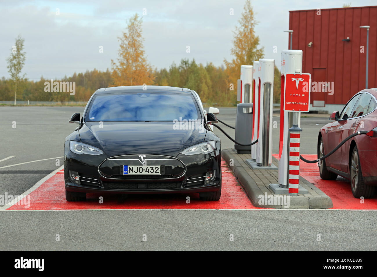 TOIJALA, FINLAND - OCTOBER 17, 2015: Three Tesla Model S cars are plugged in at Tesla Supercharger station. Supercharging - Stock Image