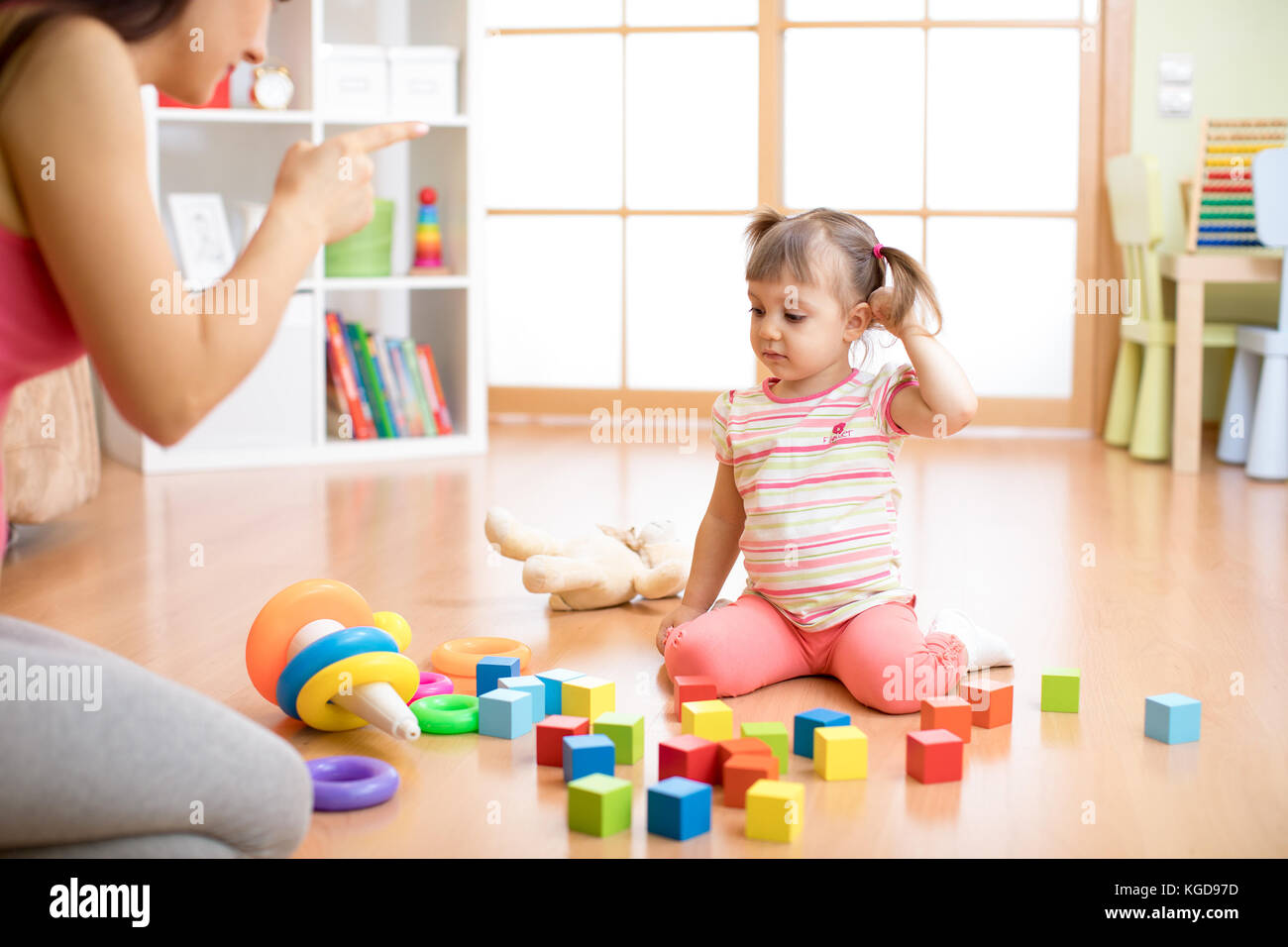 Mother see her daughter play toys messy up the living room feel angry and criticize the sadness kid girl at home. - Stock Image