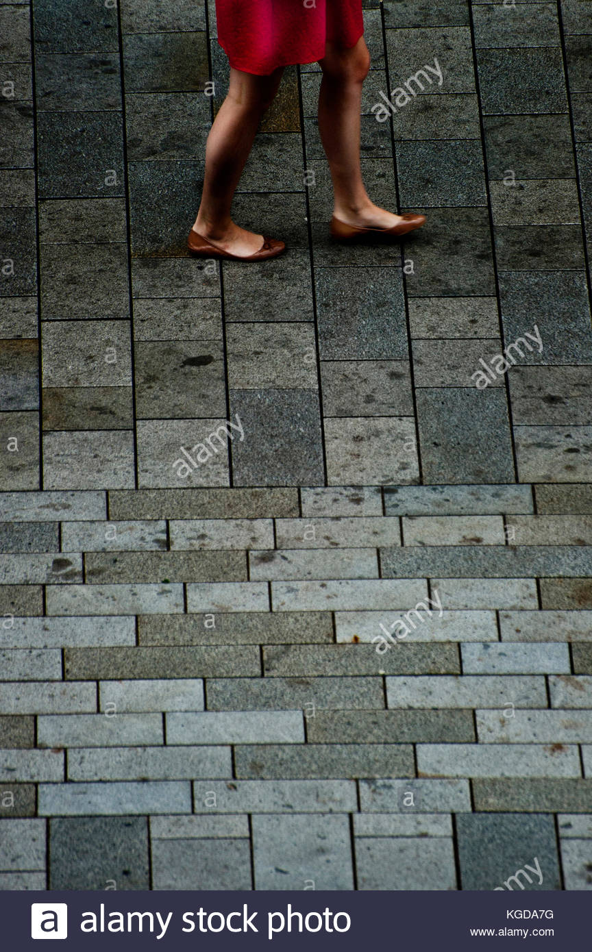legs of a woman in a summer red skirt walking - Stock Image