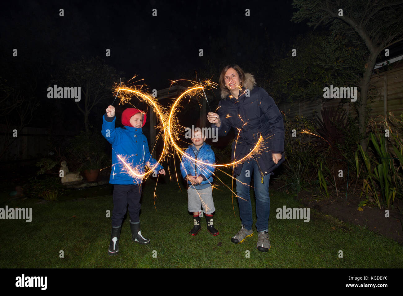 Family with hand held sparkler fireworks in a residential garden on Bonfire Night marking the anniversary of the Stock Photo