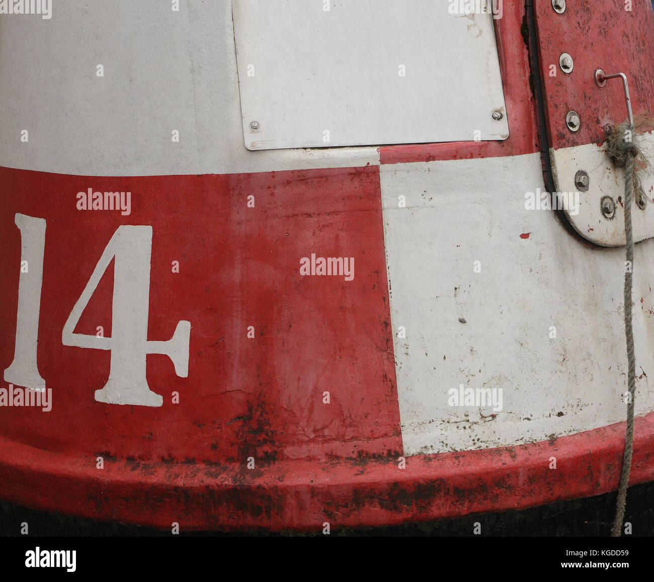 A redundant red and white chequered buoy with the number 14. Topsham, Devon, UK. - Stock Image