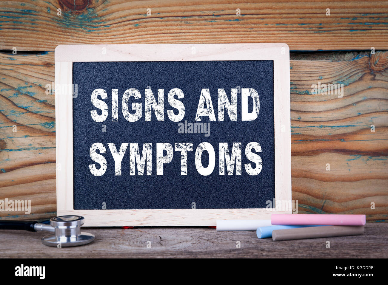 signs and symptoms. Chalkboard on a wooden background - Stock Image