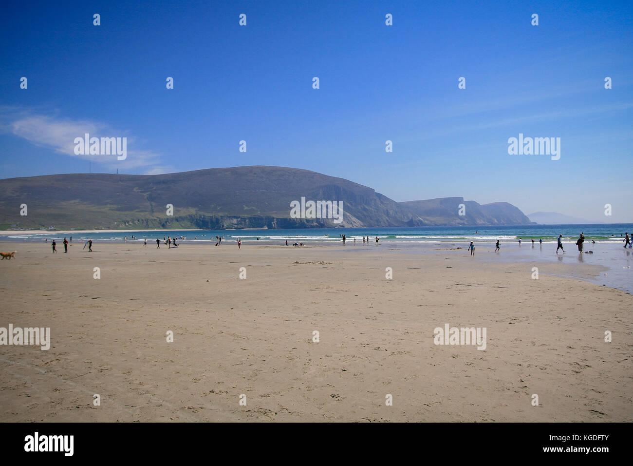 People enjoying good weather on a beautiful sandy Keel Beach in Achill Island, County Mayo, Ireland - Stock Image