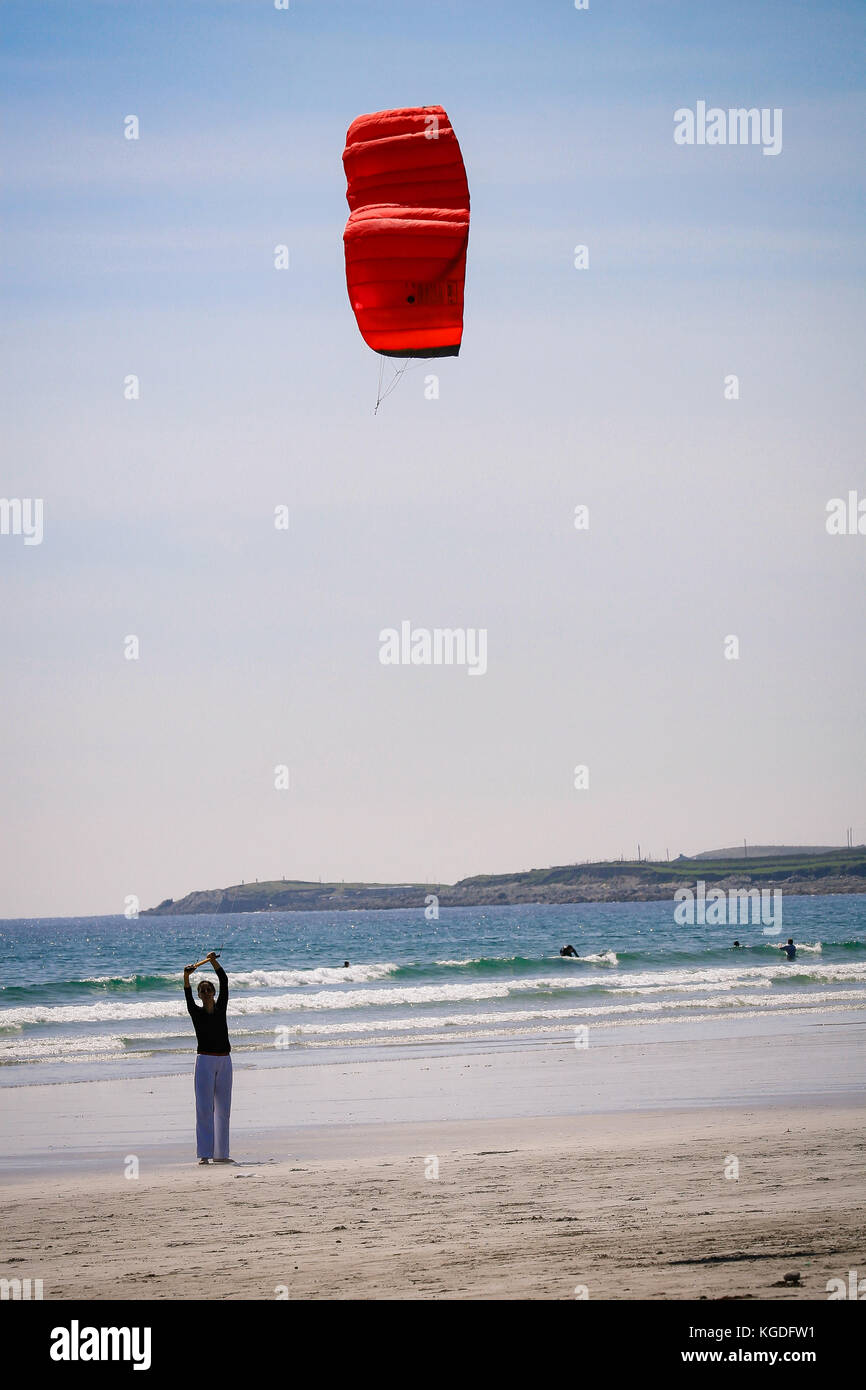 Girl flying a Parafoil Kite catching the wind on a sandy Keel Beach in Achill Island, County Mayo, Ireland - Stock Image