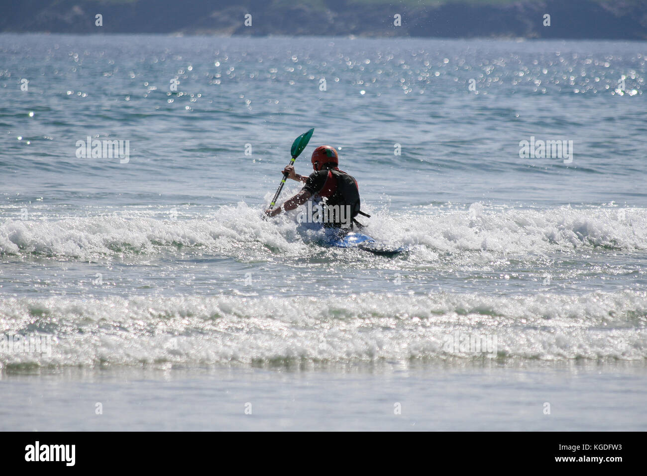 Man sea kayaking on a sunny June summer day on the Keel Beach in Keel, Achill Island, County Mayo, Ireland - Stock Image
