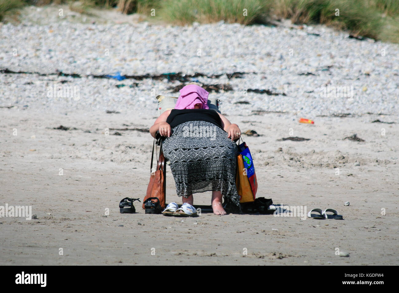 Lady laying on a chair covers her face to protect from the strong midday sun on a Keel beach in Keel, Achill Island, Stock Photo