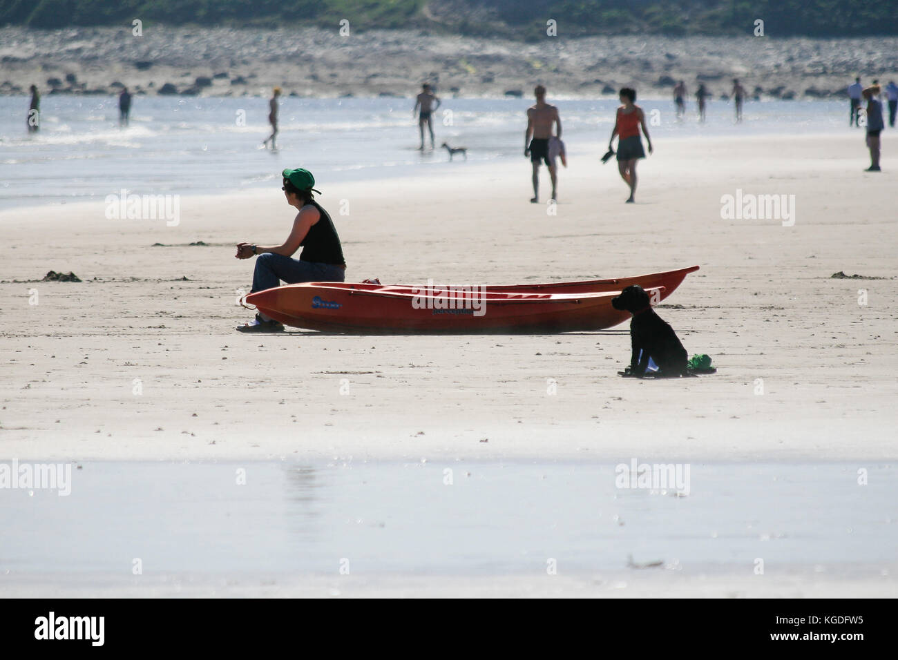 People walk and relax on a sandy Keel Beach on a hot June summer day, Achill Island, County Mayo, Ireland - Stock Image