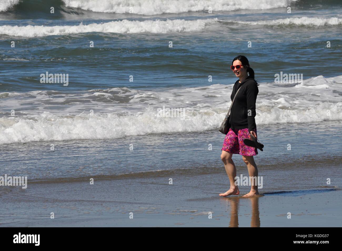 artist, Michelle Wong Clay walking on Ocean Beach in San Francisco, California - Stock Image
