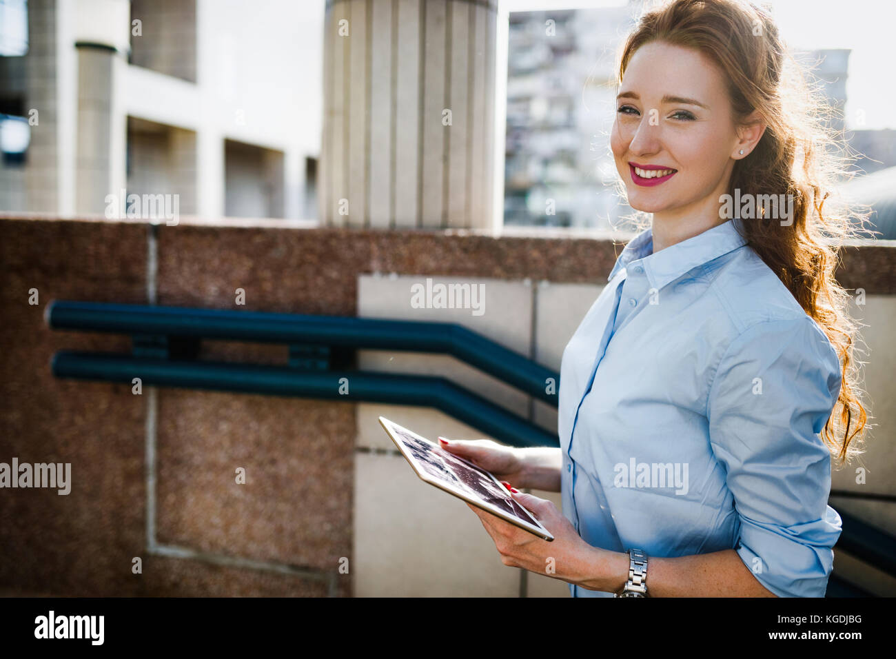 Portrait of businesswoman walking and holding tablet - Stock Image