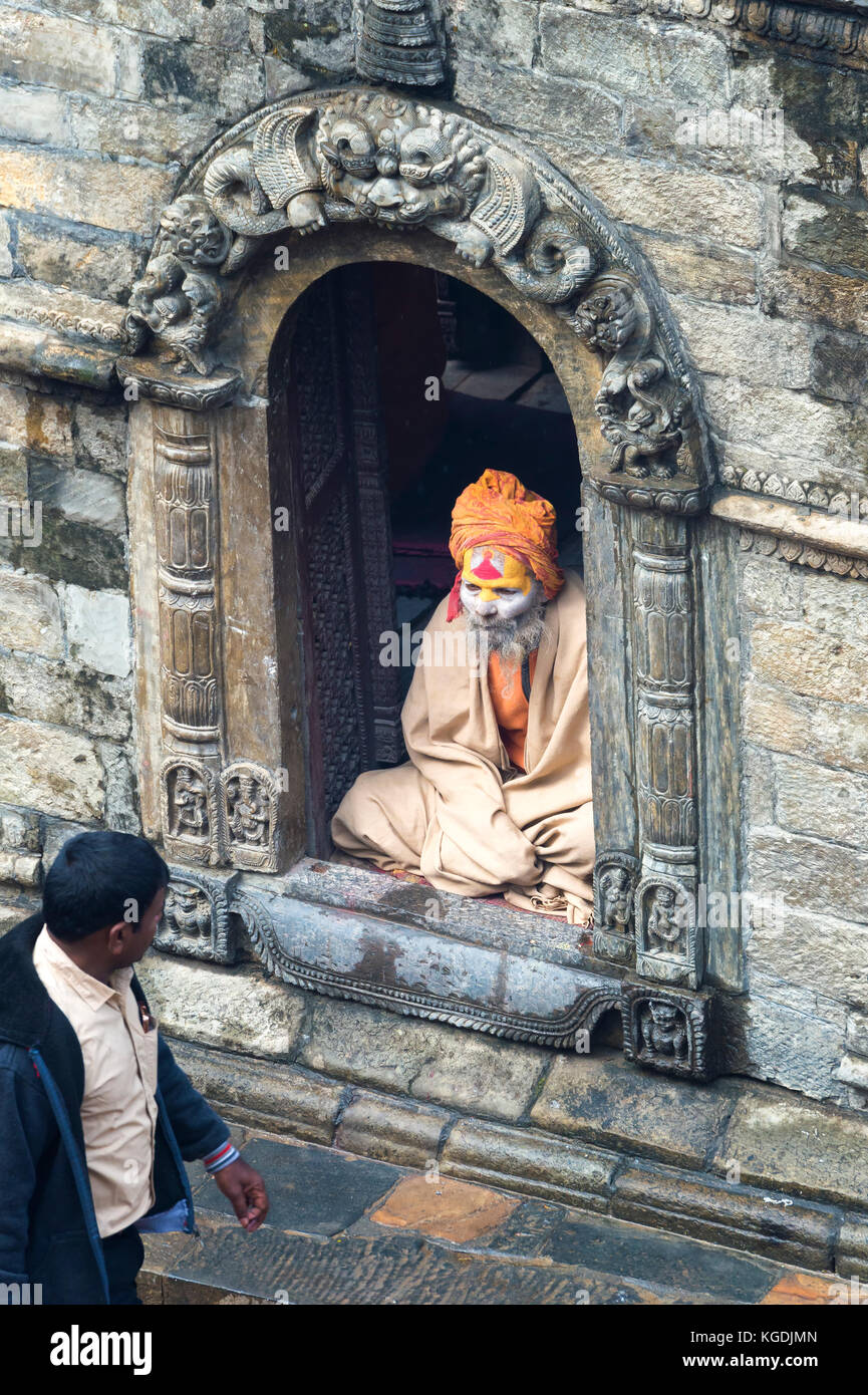 Nepalese man passing in front of an Hinduist Sadhu seated in a shrine, Holy Man, Pashupatinath Temple, Kathmandu, - Stock Image