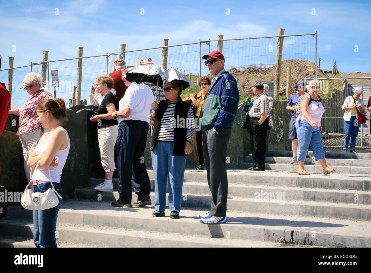 Tourists at Cliffs Of Moher taking shelter from the sun under the umbrella on a hot June summer day, Liscannor, - Stock Image