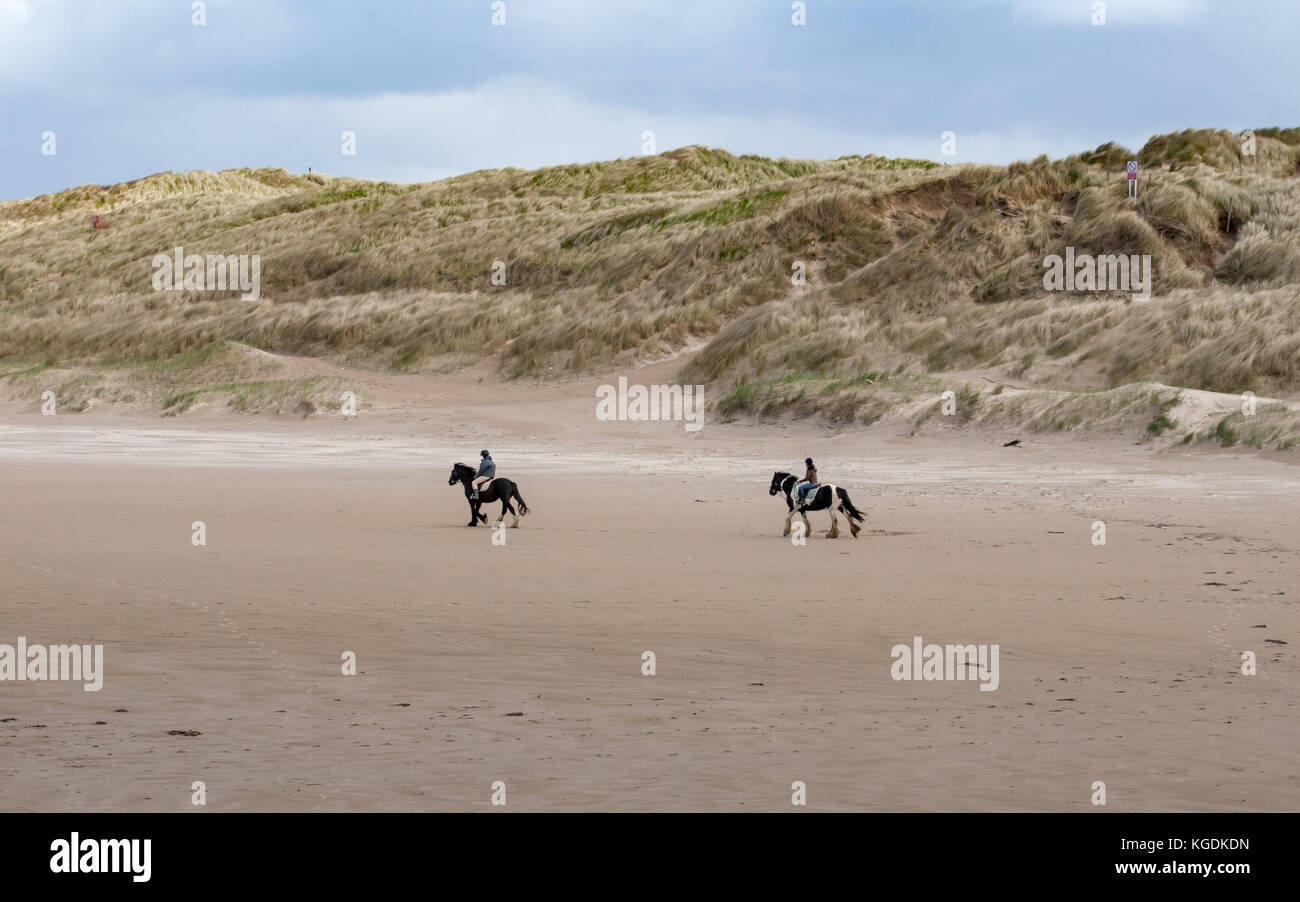 Two girls back horse riding on a sandy beach of Liscannor Bay in Lahinch, northwest coast of County Clare, Ireland - Stock Image