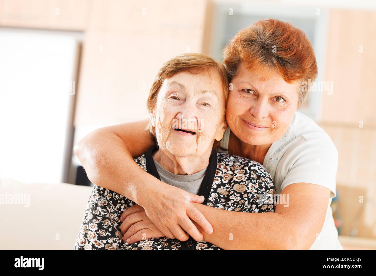Mother and daughter hugging each other - Stock Image