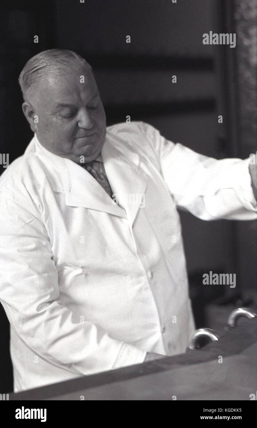 1950s, historical picture showing a close-up of a an elderly and portly pub landlord wearing a white-coat pouring Stock Photo