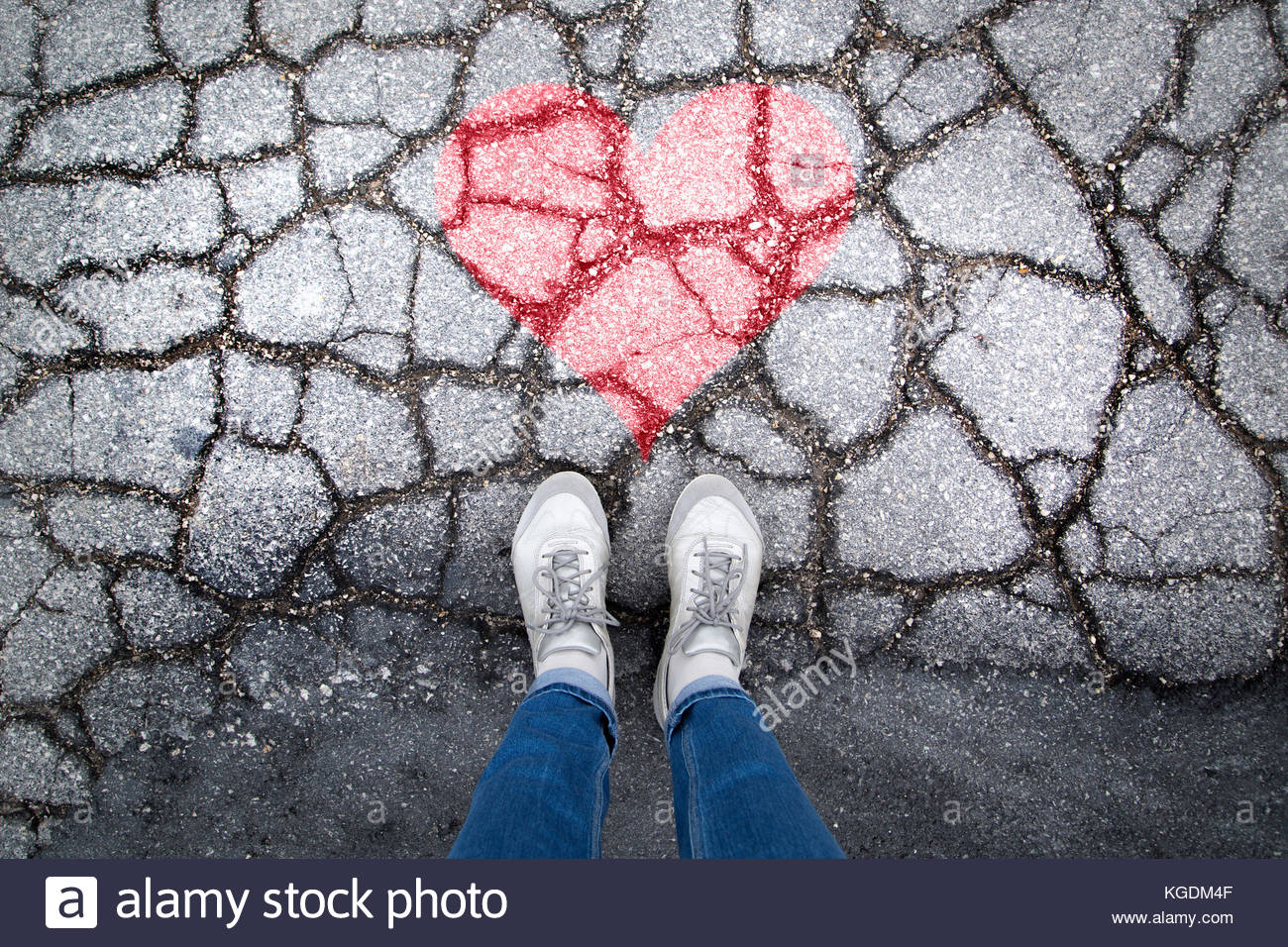 Person stands on cracked asphalt floor with painted red heart symbol. Personal perspective used. - Stock Image