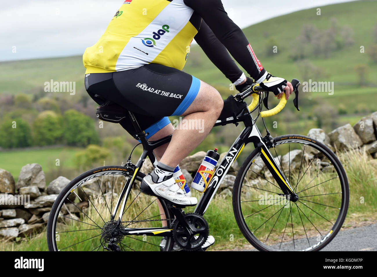 Overweight cyclist cycling up hill in Yorkshire UK - Stock Image