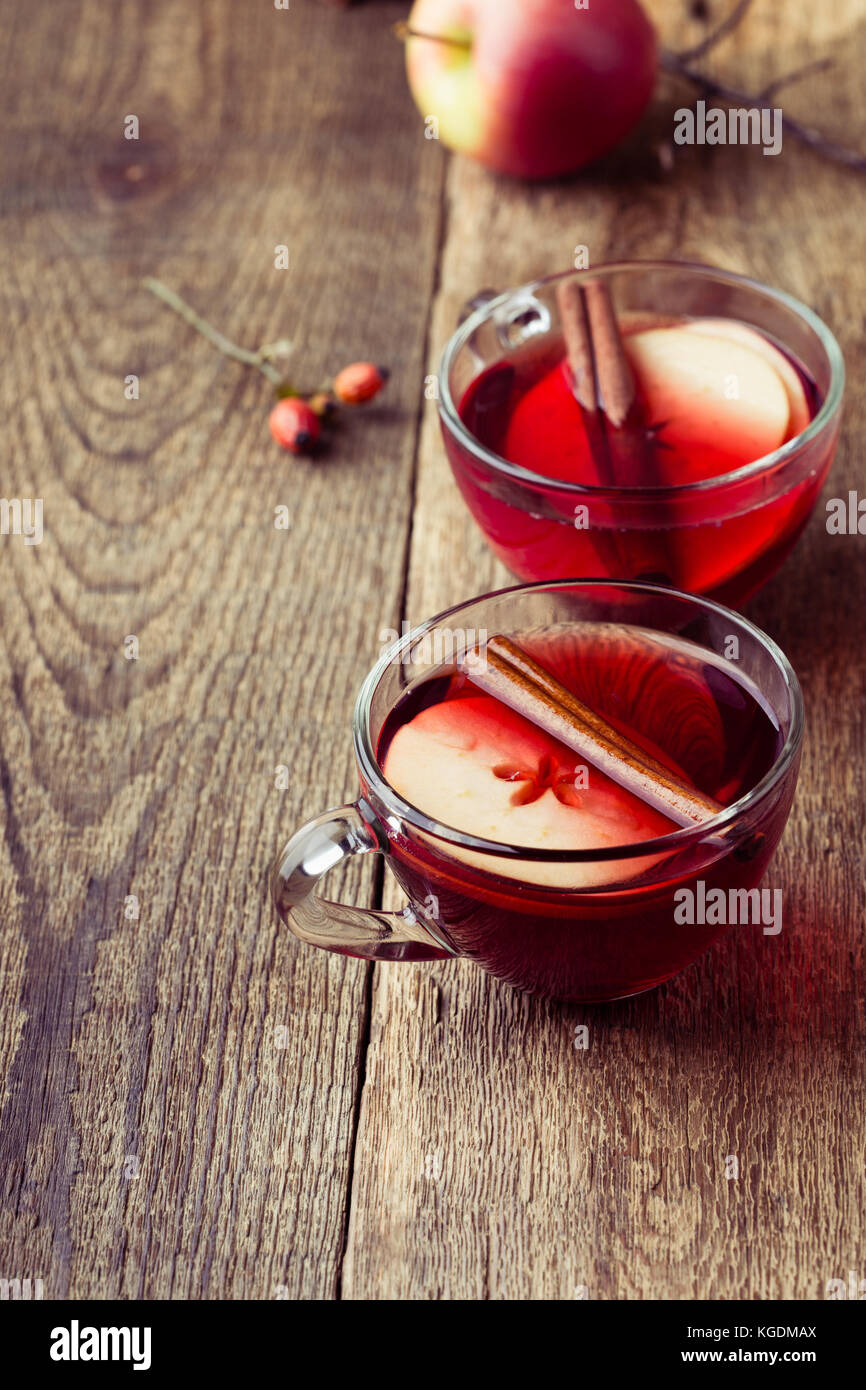 Mulled wine with apple slices in glass mugs on rustic wooden table served for two persons - Stock Image