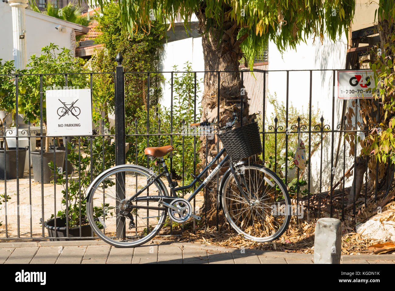 Israel The Holy Land Tel Aviv street scene Evoke Ice Maiden bike bicycle cycle padlocked to railings by no parking - Stock Image