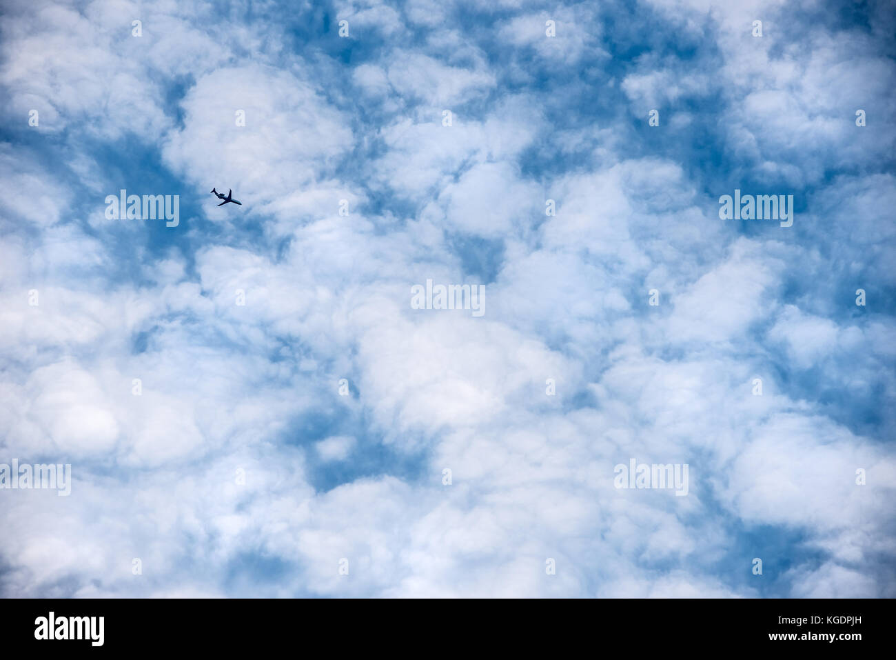 Passenger airline jet flying high overhead against a backdrop of white puffy clouds resembling cotton balls. (USA) - Stock Image