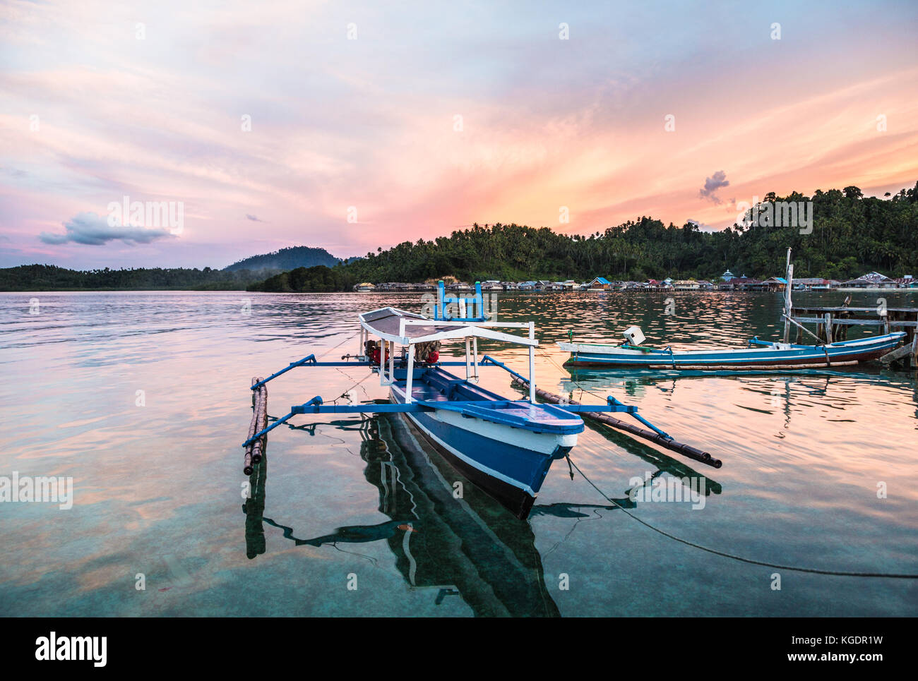 Stunning sunset over a traditional boat in Katupat in the Togian (or Togean) islands in Sulawesi, a remote corner - Stock Image