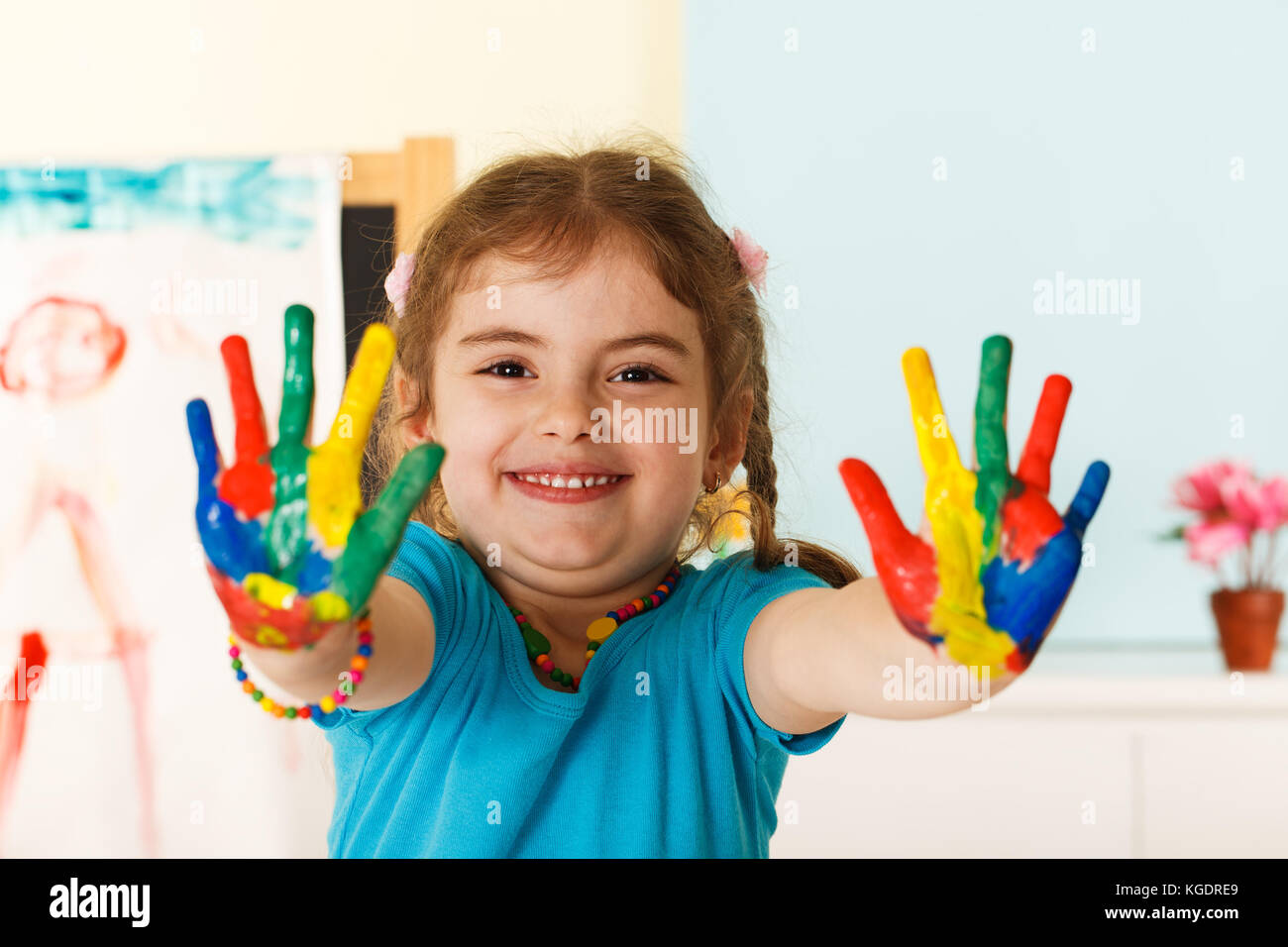 Five year old girl with hands painted in colorful paints ready for hand prints - Stock Image