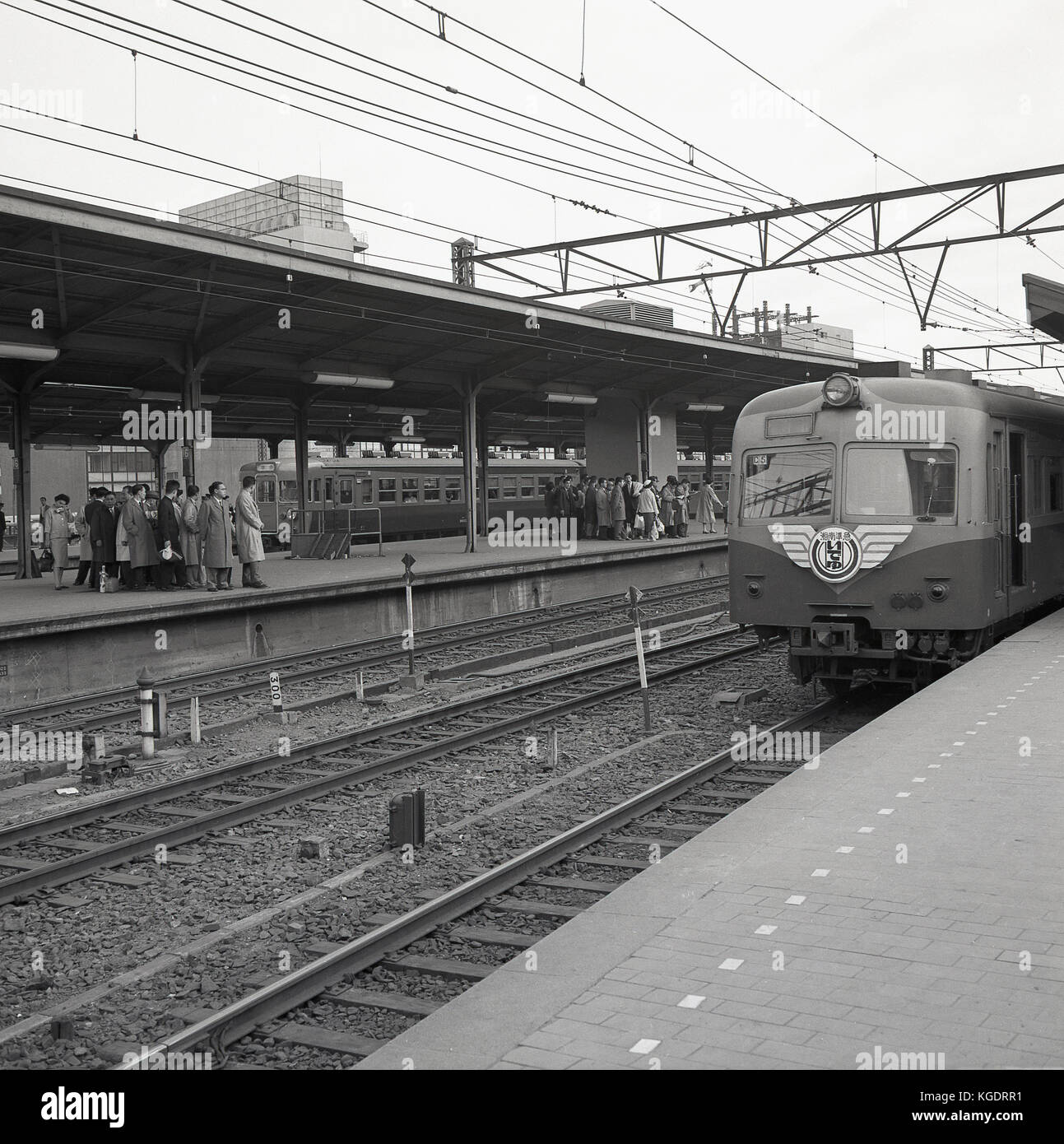 1950s, historical, an overground train arrives on one platform, while another we see japanese rail commuters have - Stock Image