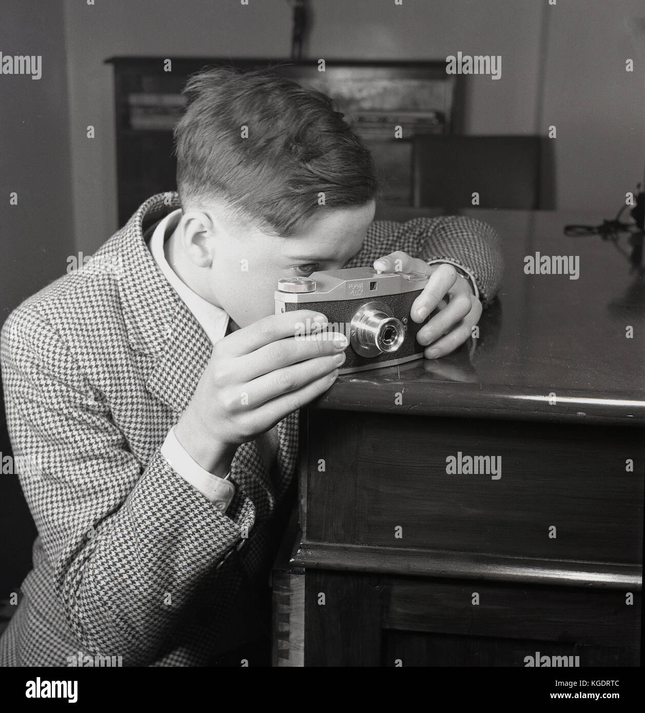 1950s, historical, young man using a corner of a cabinet for stability when taking a photograph with his Purma Plus - Stock Image