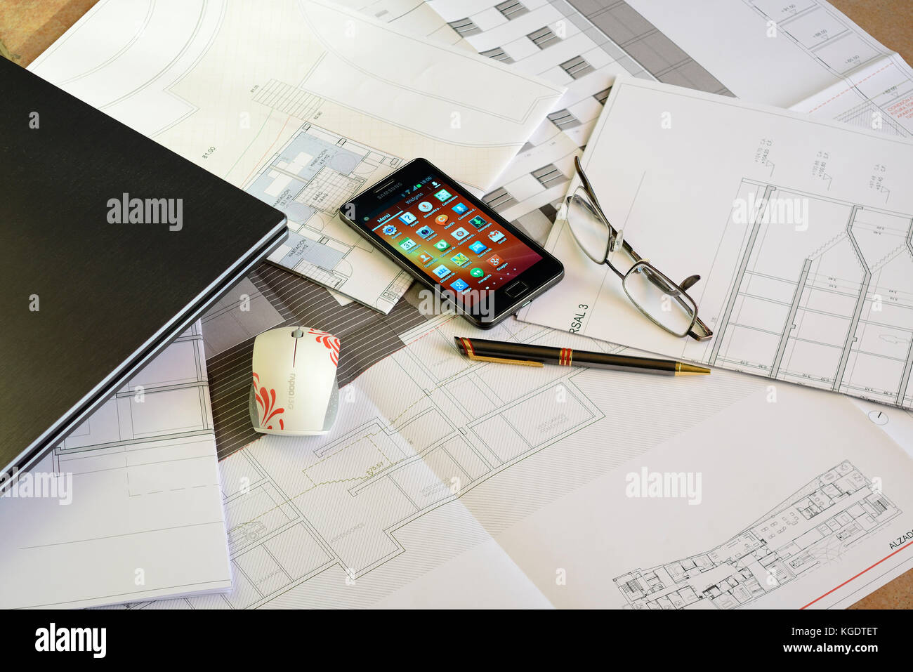 Smartphone, glasses, Pen, Laptop and Mouse over Architect plans Stock Photo