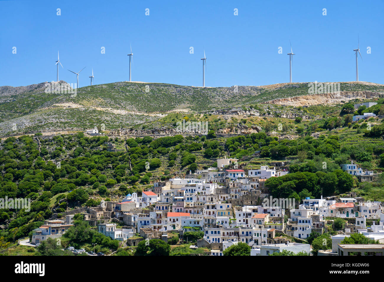 Wind turbines above a mountain village at the north of Naxos, Cyclades, Greece, Mediterranean Sea, Europe - Stock Image