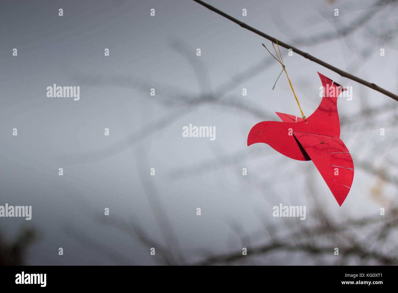 Shiny red bird ornament on a branch with cold winter sky in the background. Perfect wallpaper, with copyspace. - Stock Image