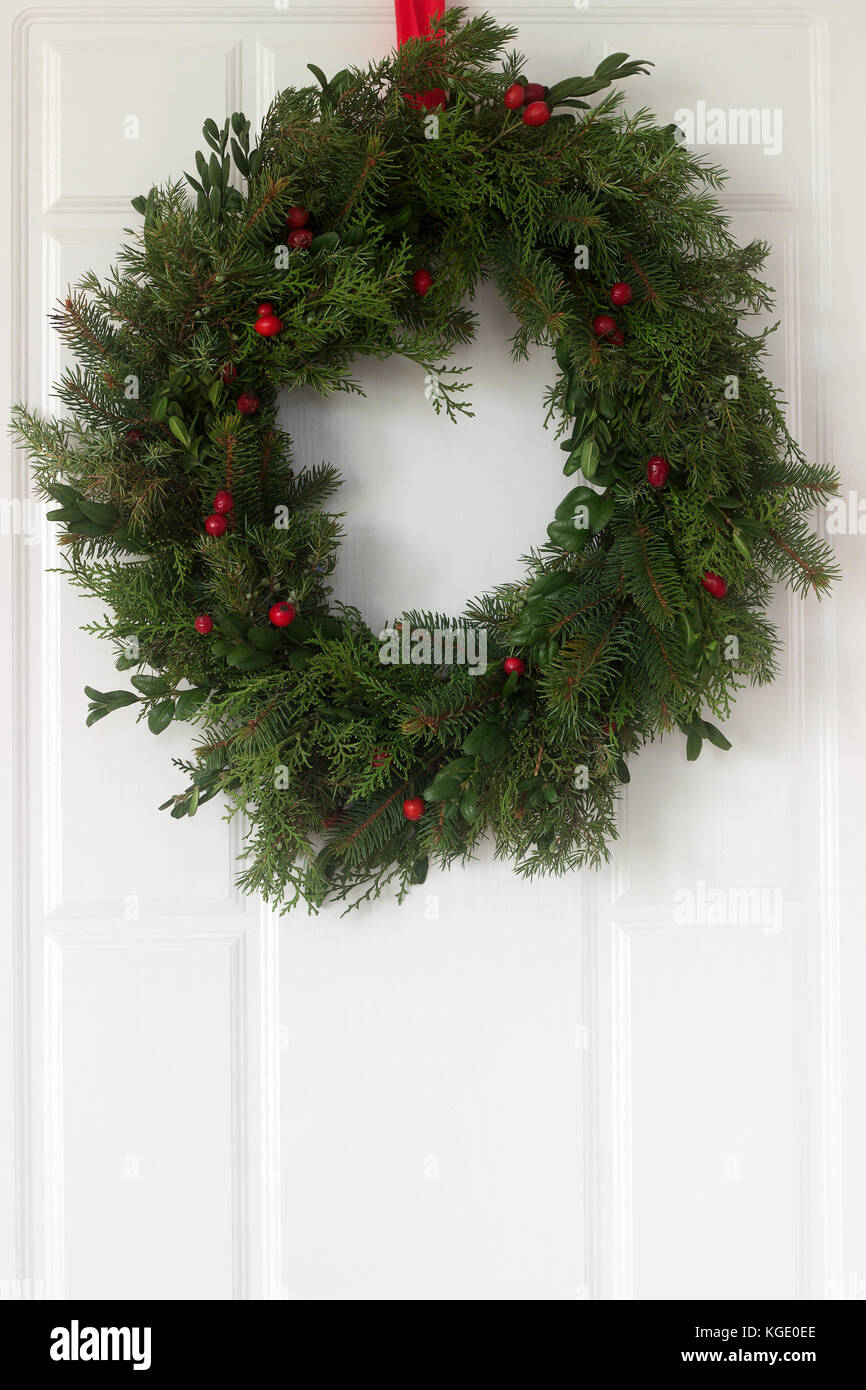 Handmade is a Christmas wreath made of spruce, thuja, juniper, boxwood and wild rose berries adorning the front - Stock Image