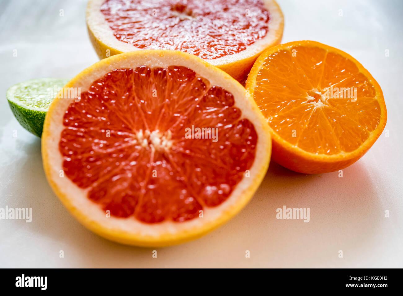 Colorful half citrus fruit, side view, closeup. Grapefruit, orange and lime fruit halves, macro, horizontal. - Stock Image